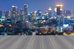 在晚上打开木地板有摘要被弄脏的bokeh城市光视图 库存图片