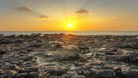 在晚上日落期间,多岩石的海滩在低潮揭露了 免版税图库摄影