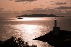 在晚上日落的灯塔 免版税库存图片