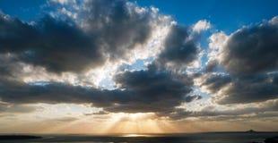 在晚上期间,太阳在云彩后落 太阳光芒早晨击穿云彩 图库摄影