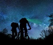 在晚上结合乘驾自行车在银河下 库存照片