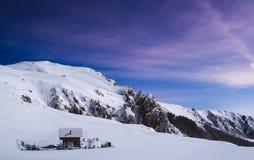 在晚上被拍摄的多雪的山顶部的浪漫原木小屋 库存图片