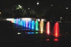 在晚上被照亮的五颜六色的喷泉 图库摄影