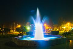 在晚上被照亮的喷泉在一个小镇 库存照片