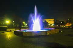 在晚上被照亮的喷泉在一个小镇 库存图片
