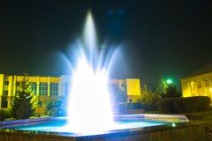 在晚上被照亮的喷泉在一个小镇 免版税库存图片