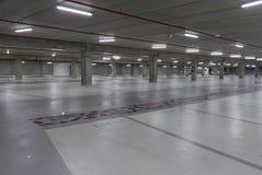 在晚上被照亮的空的地下停车场 免版税库存图片