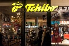 在晚上被采取的他们的慕尼黑主要商店的Tchibo商标 Tchibo是咖啡零售商和cafés德国链子  免版税库存照片