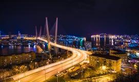 在晚上观看城市,横跨海湾的桥梁在晚上,有很多明亮的光 免版税图库摄影