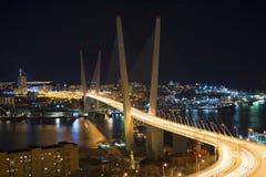 在晚上观看城市,横跨海湾的桥梁在晚上,有很多明亮的光 免版税库存照片