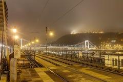 在晚上调整铁路轨道在布达佩斯有著名Gellert小山的下位tu多瑙河在背景中 免版税库存图片