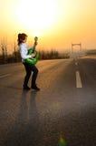 在晚上,弹在路的女孩吉他 免版税库存图片