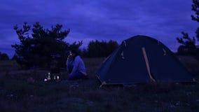 在晚上,男人和妇女是在帐篷和篝火油炸物肉 股票视频