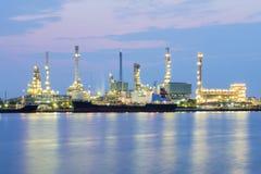 在晚上,重的工业制造业背景上油工厂河边 免版税库存图片