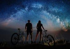 在晚上结合有登山车的骑自行车者在满天星斗的天空下 库存照片