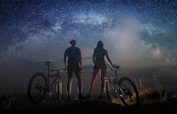 在晚上结合有登山车的骑自行车者在满天星斗的天空下 库存图片