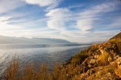 在晚上erhai湖,有美丽的卷积云彩和天空蔚蓝的 免版税库存图片
