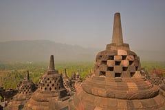在晚日出期间的婆罗浮屠巨人Stupas充满在森林中的有薄雾的感觉在背景中 库存照片