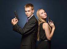 在晚礼服的美好的间谍夫妇与枪 免版税库存图片