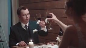 在晚餐在餐馆,慢动作期间,年轻人和他的美女喝酒 股票录像
