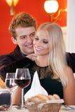 在晚餐日期期间,年轻夫妇美好的片刻 免版税图库摄影