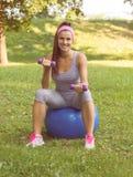 在普拉提球的健身健康微笑的少妇锻炼 免版税图库摄影