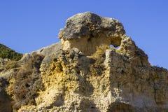 在普腊亚da Oura海滩的典型的被暴露的沉淀沙子石头峭壁面孔在Albuferia 库存图片