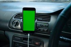 在普通汽车的仪表板的智能手机 免版税库存照片