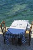 在晴天制表和街道克利特的希腊餐馆两把椅子  免版税库存照片