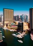 在晴天期间,与水运河,迪拜,阿联酋的惊人的五颜六色的迪拜小游艇船坞地平线 库存照片