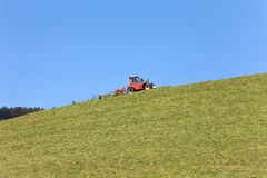 在晴天期间,农夫用于的机械工具移动在草甸的干草, 免版税库存照片