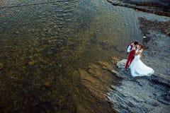 在晴天期间,快乐的时髦的新婚佳偶夫妇在河岸拥抱 在蓝色被定调子的工具视图之上 免版税库存图片