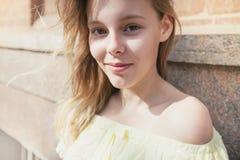 在晴朗的城市街道上的微笑的年轻俏丽的女孩 库存照片