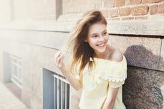 在晴朗的城市街道上的微笑的年轻俏丽的女孩 图库摄影