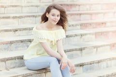 在晴朗的城市街道上的微笑的年轻俏丽的女孩 免版税图库摄影