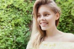 在晴朗的城市街道上的微笑的年轻俏丽的女孩 免版税库存图片