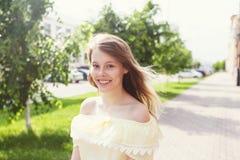 在晴朗的城市街道上的微笑的年轻俏丽的女孩 免版税库存照片