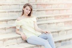 在晴朗的城市街道上的美丽的年轻俏丽的女孩 库存图片