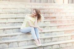 在晴朗的城市街道上的美丽的年轻俏丽的女孩 库存照片