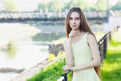 在晴朗的城市街道上的美丽的年轻俏丽的女孩 免版税图库摄影