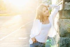 在晴朗的城市街道上的美丽的年轻俏丽的女孩 免版税库存照片