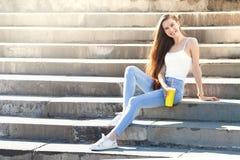 在晴朗的城市街道上的美丽的年轻俏丽的女孩 免版税库存图片