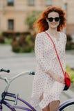 在晴朗的大风天期间,高兴的红发妇女照片有柔和的微笑的,在城市街道上花悠闲时间骑马自行车,佩带 免版税库存图片