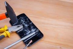 在智能手机上是螺丝刀和钳子和锤子 在一个木背景 免版税库存照片