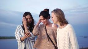 在智能手机上看东西时,三个快乐、漂亮的年轻白人女性最好的朋友笑着 股票录像
