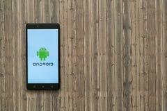 在智能手机屏幕上的机器人商标在木背景 免版税库存图片