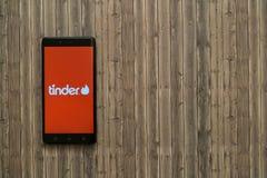 在智能手机屏幕上的火种商标在木背景 免版税图库摄影