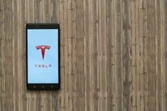 在智能手机屏幕上的特斯拉商标在木背景 免版税库存图片