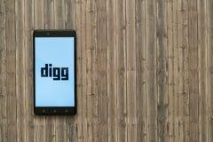 在智能手机屏幕上的Digg商标在木背景 免版税图库摄影
