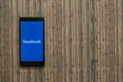 在智能手机屏幕上的Facebook商标在木背景 库存照片